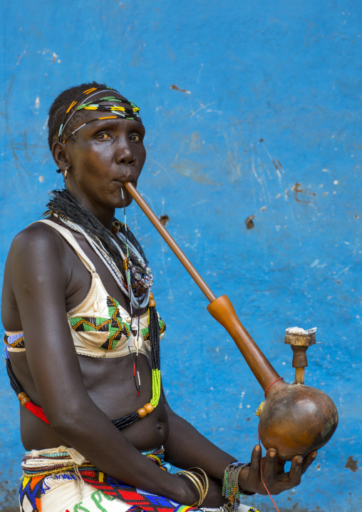 Woman Smoking A Waterpipe From Anuak Tribe In Traditional Clothing, Gambela, Ethiopia