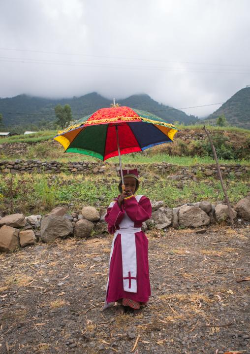 Boy collecting money in an umbrella to build a new church, Semien wollo zone, Woldia, Ethiopia
