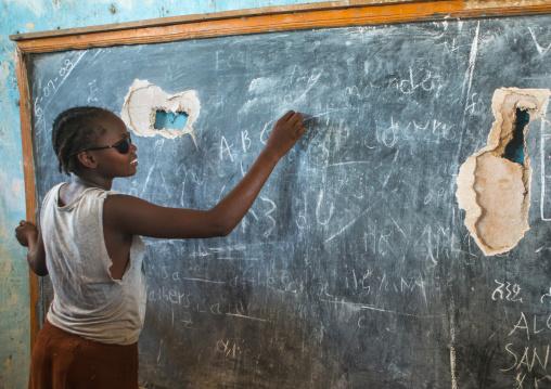 A nyangatom tribe teenage girl with sunglasses writes on a chalkboard, Omo valley, Kangate, Ethiopia