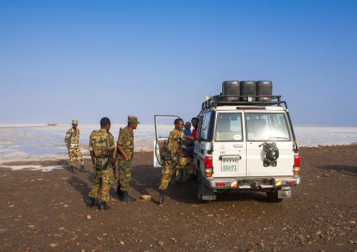 Policemen and a tourist four wheels on a salt lake, Afar region, Dallol, Ethiopia