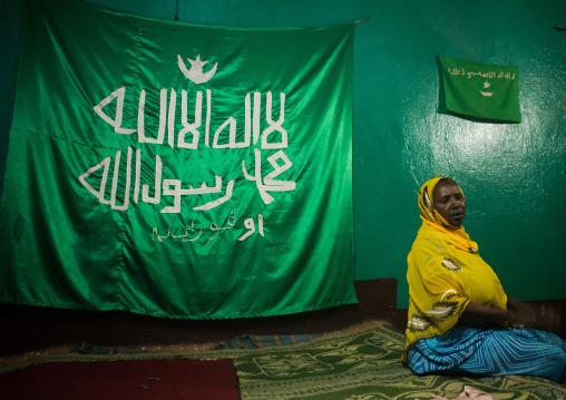 Sufi woman worshipper in front of islamic flag, Harari region, Harar, Ethiopia