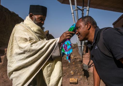 Ethiopian priest blessing a visitor during kidane mehret orthodox celebration, Amhara region, Lalibela, Ethiopia