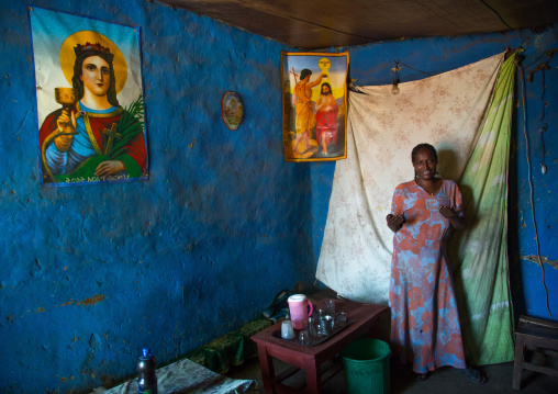 Woman inside her house decorated with religious posters, Omo valley, Jinka, Ethiopia