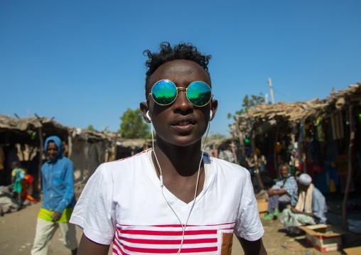 Portrait of an Afar tribe teenager with sunglasses in the street, Afar region, Assaita, Ethiopia