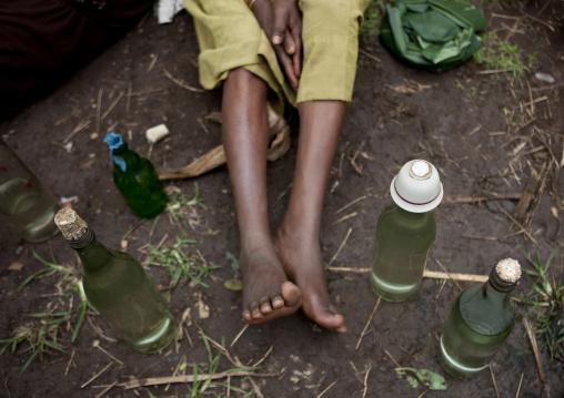 Legs between alcohol bottles, Tum market, Omo valley, Ethiopia