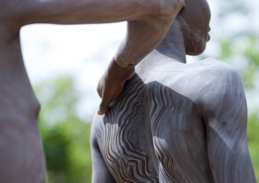 Clay body paintings on Suri warriors before donga stick fighting, Turgit village, Omo valley, Ethiopia