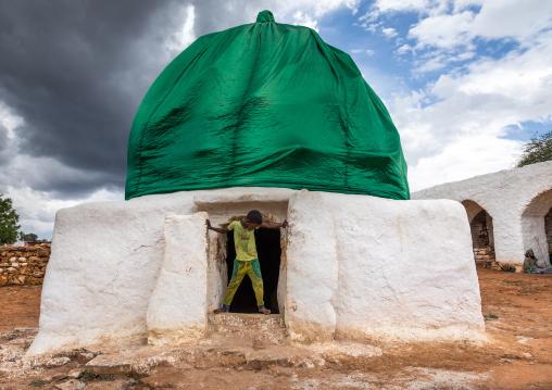 Oromo pilgrim boy in front of a shrine with green dome, Oromia, Sheik Hussein, Ethiopia