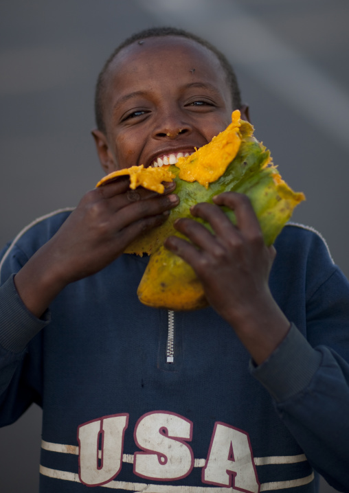 Boy eating a papaya fruit, Gourague, Area, Ethiopia
