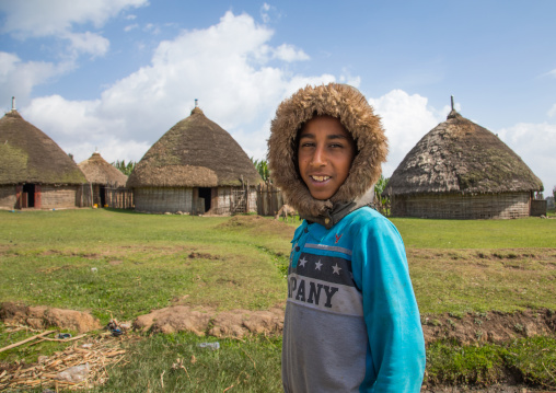 Boy with a rain hood in front of a Gurage traditional houses with thatched roofs, Gurage Zone, Butajira, Ethiopia