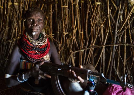 Nyangatom tribe woman holding a kalashnikov in her hut, Omo valley, Kangate, Ethiopia