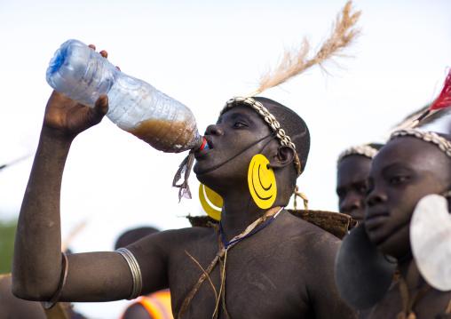 Bodi tribe fat man drinking milk during Kael ceremony, Omo valley, Hana Mursi, Ethiopia