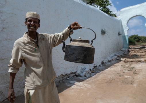 Muslim man holding a huge teapot, Harari Region, Harar, Ethiopia