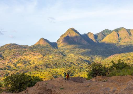 Suri tribe couple in front of a mountain landscape, Omo valley, Kibish, Ethiopia