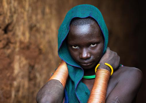 Portrait of a suri tribe young woman with impressive bracelets, Omo valley, Kibish, Ethiopia