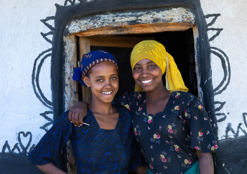 Smiling raya tribe gilrs at the entrance of a decorated hut, Afar Region, Chifra, Ethiopia