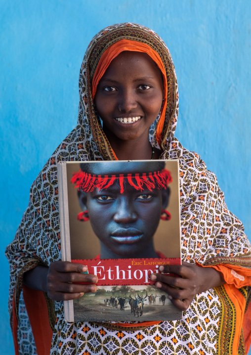 Portrait of a veiled smiling afar tribe girl with sharpened teeth holding eric lafforgue book, Afar Region, Afambo, Ethiopia