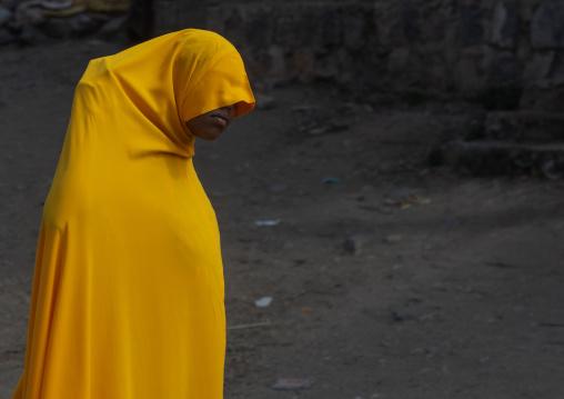 Ethiopian woman in yellow burqa walking in the street, Oromia, Karamile, Ethiopia