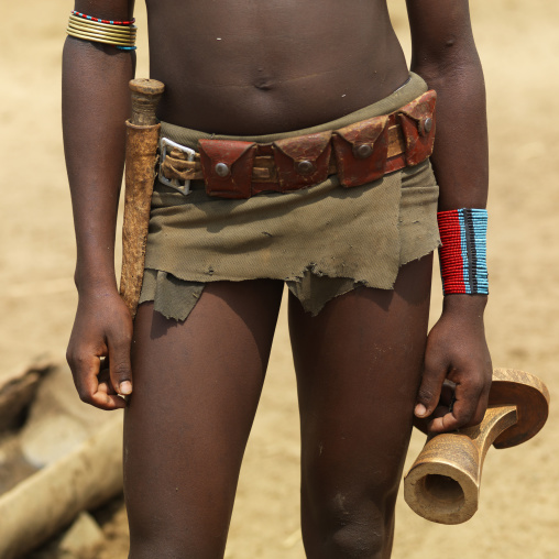 Tsemay woman close up loincloth and belt with a headrest in her hand, Omo valley, Ethiopia