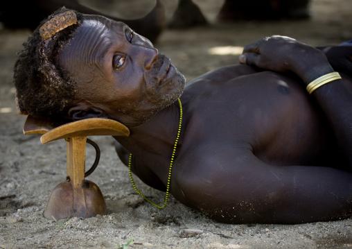 Portrait Of A Karo Man Laying Down On His Headrest, Korcho Village, Omo Valley, Ethiopia