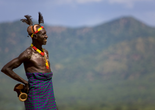 Portrait Of A Smiling Karo Tribe Man With Mud Bun And Headrest With Mountains In The Backgroung, Korcho Village, Omo Valley, Ethiopia