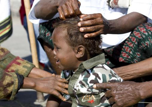 Baby having hair shaved at aid el kebir celebration, Assaita, Afar regional state, Ethiopia