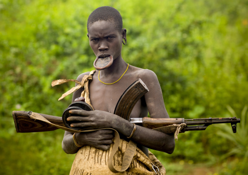 Mursi Tribe Woman With A Lip Plate, A  Kalashnikov Rifle And Two Clay Plates In Her Hands, Omo Valley, Ethiopia