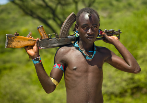Young tsemay tribe man with beaded jewels carrying kalashnikov rifle on his shoulders, Omo valley, Ethiopia