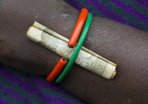 Detail of a bracelet with a birr note on a Suri tribe woman, Kibish, Omo valley, Ethiopia