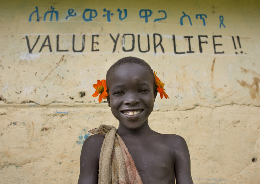 Young Suri boy leaning against a wall of a school, Covered with amharic and english writing, Tulgit, Omo valley, Ethiopia
