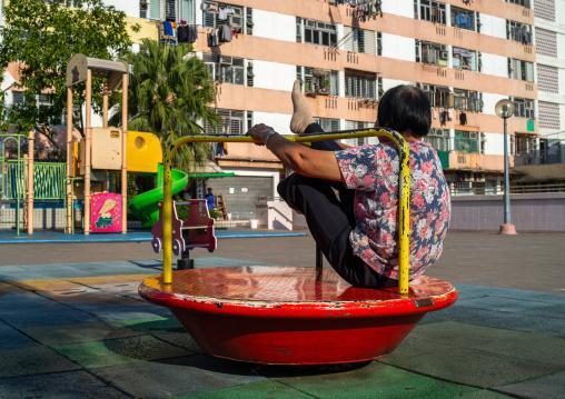 Chinese woman maknig gymnastic on a playground, Kowloon, Hong Kong, China