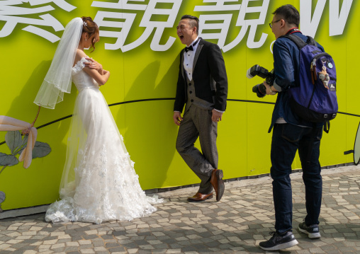Bride and groom with a photographer, Kowloon, Hong Kong, China