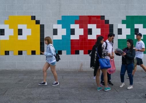 Invader pac-man mosaics on a wall in the street, Kowloon, Hong Kong, China