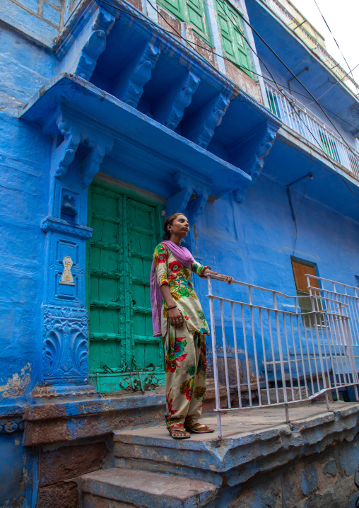 Indian girl standing in front of an old blue house of a brahmin, Rajasthan, Jodhpur, India