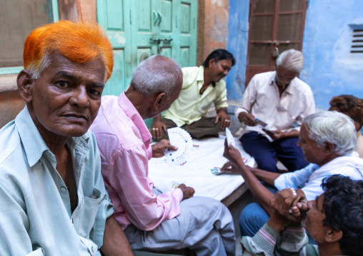 Portrait of a man with ginger hair with friends playing cards, Rajasthan, Jodhpur, India
