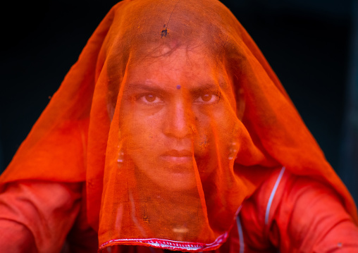 Portrait of a rajasthani woman hidding her face under a orange sari, Rajasthan, Jaisalmer, India