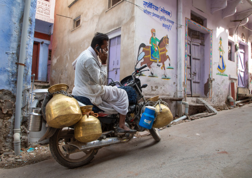 Indian man calling on his phone to deliver fresh milk with his motorbike, Rajasthan, Bundi, India