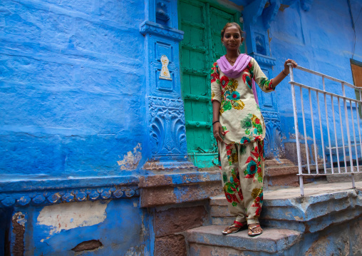 Portrait of a rajasthani teenage girl in traditional sari in front of a blue house, Rajasthan, Jodhpur, India