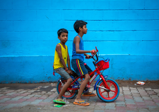 Indian boys riding a bicycle in front of a blue wall, Rajasthan, Jodhpur, India
