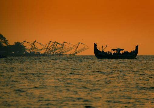 Boat Sailing Close To Chinese Fishing Nets In Silhouette At Sunset, Kochi, India