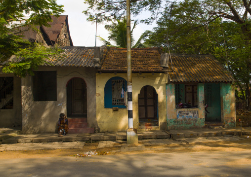 Old Woman Sitting On Doorstep Of A Old Decrepit House In The Street Of Pondicherry, India