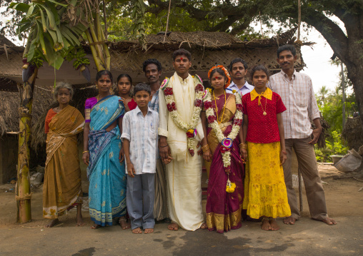 Young Bride And Groom  Dressed For The Ceremony And Adorned With Flower Garlands Posing Surrounded By Family, Pondicherry, India