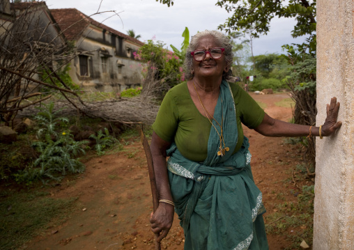 Old Woman With Glasses Holding Herself Against A Wall In A Garden In Kanadukathan Chettinad, India