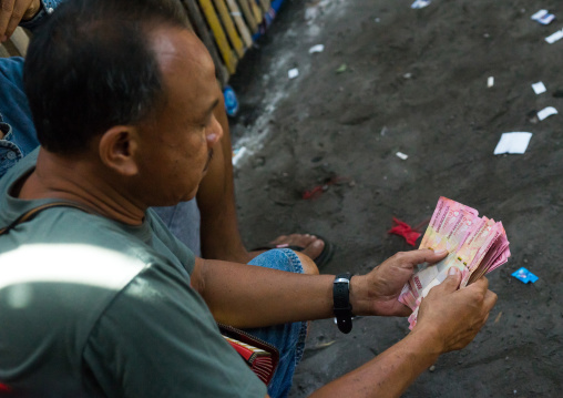 Men Taking The Money For The Bets During A Cockfigting Event