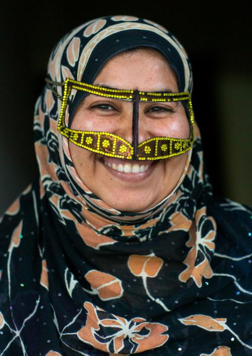 a smiling bandari woman wearing a traditional mask called the burqa with a moustache shape, Qeshm Island, Salakh, Iran