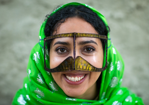 A smiling bandari woman wearing a traditional mask called the burqa with a moustache shape, Qeshm island, Salakh, Iran