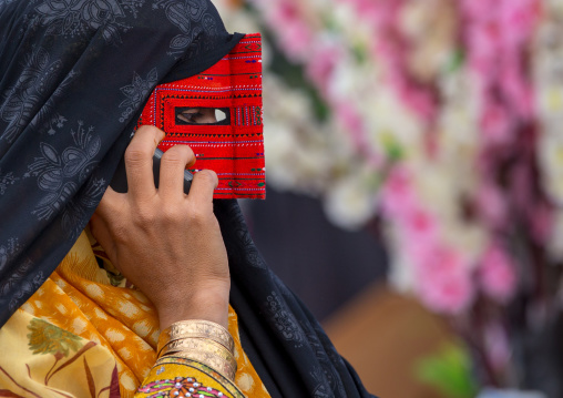 A bandari woman wearing a traditional mask called the burqa calling on a mobile phone, Hormozgan, Minab, Iran