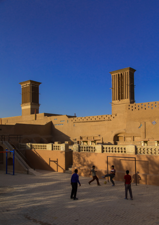 Children playing football in front of ind towers used as a natural cooling system in iranian traditional architecture, Yazd province, Yazd, Iran