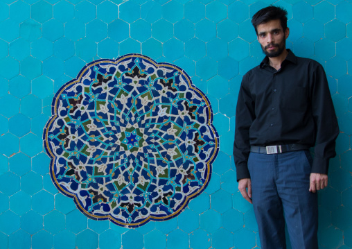 Iranian shiite man in jameh mosque in front of a blue mosaic, Yazd province, Yazd, Iran