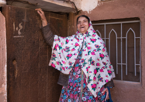 Portrait of an iranian woman wearing traditional floreal chador in front of an old wooden door, Natanz County, Abyaneh, Iran