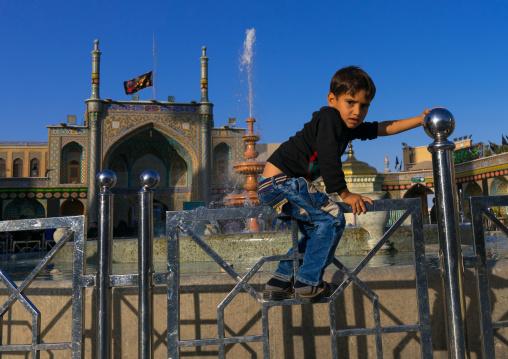 Boy jumping a fence in Fatima al-Masumeh shrine, Central County, Qom, Iran